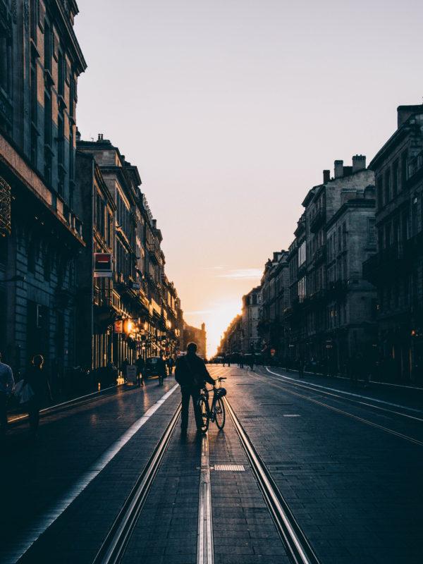 Voici une photographie d'un jeune homme dans une rue regardant le couché de soleil